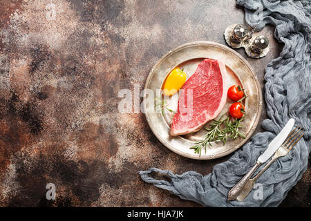 Fresh raw Prime Black Angus beef strip steaks on metal plate over dark rustic concrete background, top view. Ingredients - Stock Photo