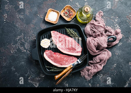 Fresh raw Prime Black Angus beef strip steaks on grill pan over dark rustic concrete background, top view. Ingredients - Stock Photo