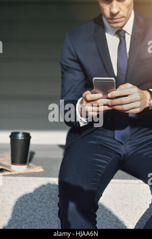 Man works with his cell phone. Vertical outdoors shot - Stock Photo