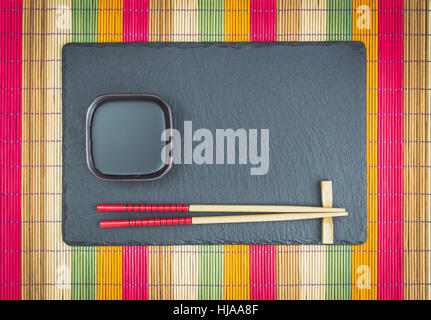 Chopsticks  and soy sauce on slate top view - Stock Photo