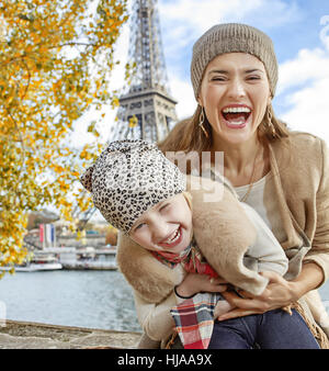 Autumn getaways in Paris with family. happy mother and child tourists on embankment in Paris, France having fun - Stock Photo