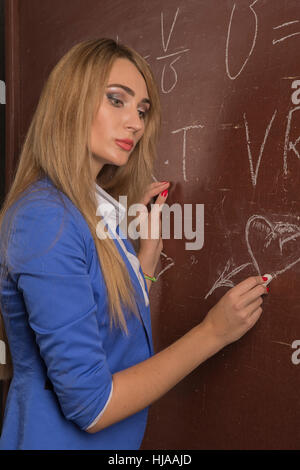 Thoughtful girl with a headache posing against a background of chalkboard. - Stock Photo