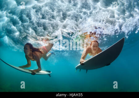 Group of active girls in action. Surfer women with surf board dive underwater under breaking wave. Water sport, - Stock Photo