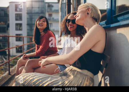 Three young female friends sitting in balcony and having fun. Women relaxing outdoors and chatting. - Stock Photo