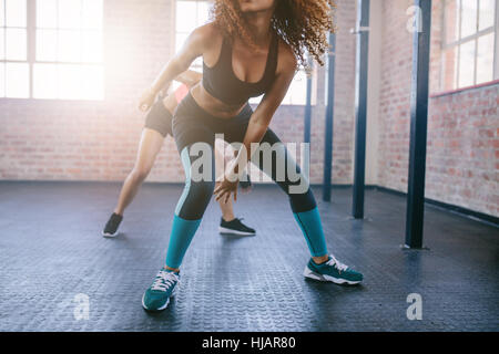 Cropped shot of young females doing running workout in the gym.  Focus on legs of women. - Stock Photo