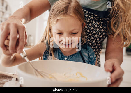 Beautiful little girl with her mother mixing batter in bowl and smiling. Mother and daughter in kitchen preparing - Stock Photo