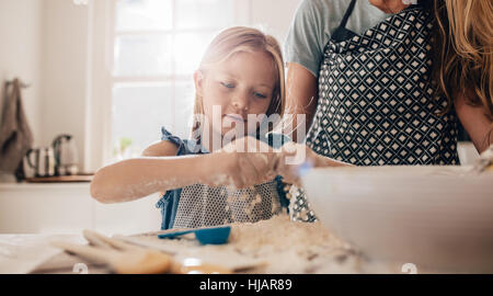 Cute little girl preparing dough in kitchen with her mother. Young girl learning to cook. - Stock Photo