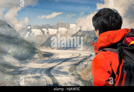 Lone male climber looking out over Aletsch Glacier, Canton Wallis, Switzerland - Stock Photo