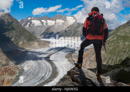 Rear view of lone male climber looking out over Aletsch Glacier, Canton Wallis, Switzerland - Stock Photo