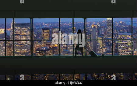 Silhouetted woman crossing city footbridge over New York cityscape at night, USA - Stock Photo