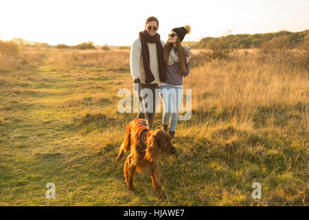 Young couple walking dog in field - Stock Photo