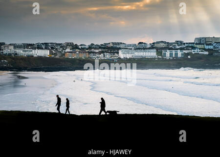 People seen in silhouette as they walk along the coastal path overlooking Fistral Beach in Cornwall, England, UK. - Stock Photo