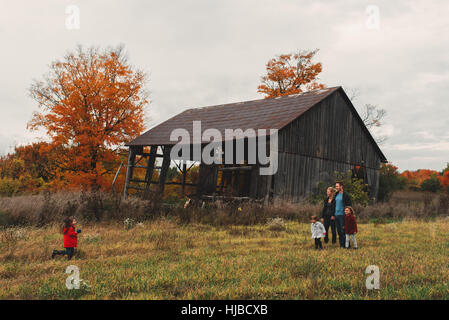 Mid adult family with three daughters strolling in rural field - Stock Photo