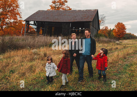 Mid adult family with three daughters holding hands and strolling in rural field - Stock Photo