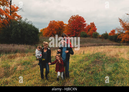 Mid adult family with three daughters strolling together in rural field - Stock Photo