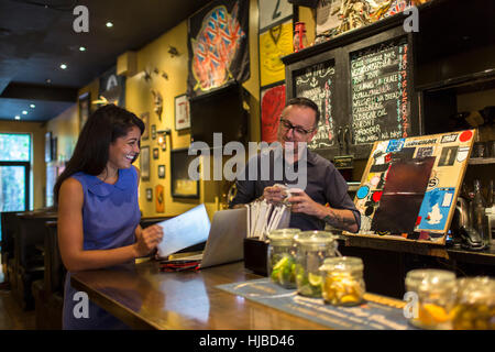 Barman laughing with female customer at public house counter - Stock Photo