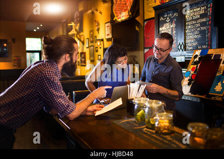Barman reading menu with young couple at public house counter - Stock Photo