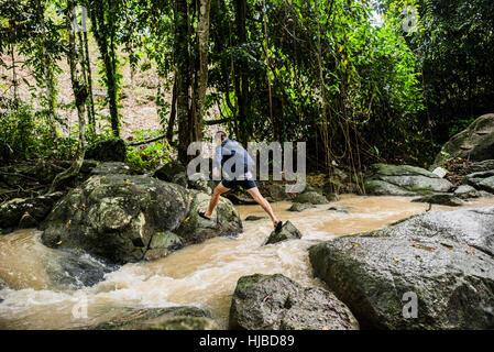 Young man crossing stream, Secret Buddha Garden, Koh Samui, Thailand - Stock Photo
