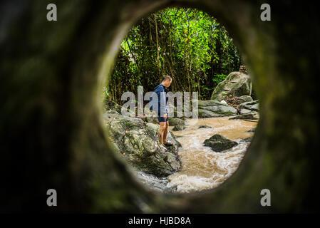 Young man watching flowing stream, Secret Buddha Garden, Koh Samui, Thailand - Stock Photo
