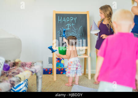 Toddler playing with balloon at blackboard at birthday party - Stock Photo