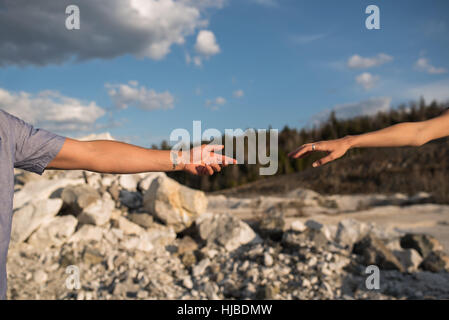 Couple reaching hands out to each other, Ottawa, Ontario - Stock Photo