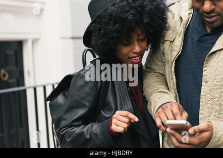 Couple in street looking at smartphone - Stock Photo
