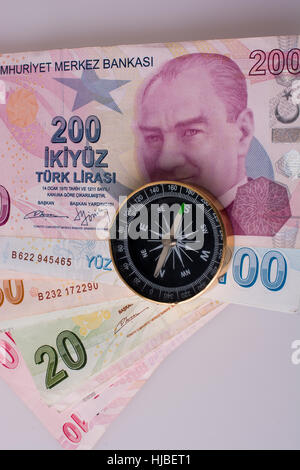 Turkish Lira banknotes by the side of a compass on white background - Stock Photo