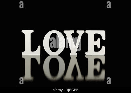 Word love, wooden letters on black background with reflection. - Stock Photo