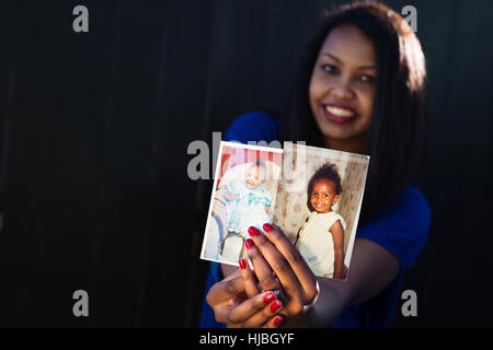 Pretty girl posing holding the pictures of when she was a toddler/baby - Stock Photo