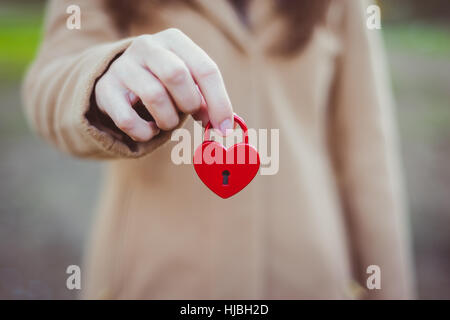 Female hand holds closed red padlock in heart shape - Stock Photo