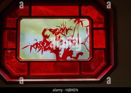 Transparent window with Chinese art surrounded by red frame. - Stock Photo