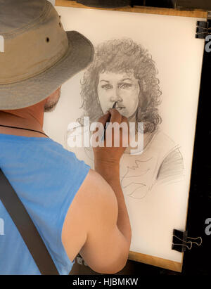 Street artist at work, drawing a portrait of a pretty woman with curly hair, on Charles Bridge, Prague 1, Czech - Stock Photo