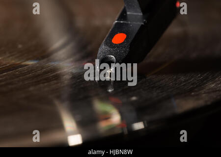 Spinning vinyl record on turntable with motion blur, closeup on stylus needle and head shell - Stock Photo