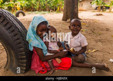 Uzi Island, Zanzibar, Tanzania - October 2016: Small children are hanging around instead of attending not existing - Stock Photo
