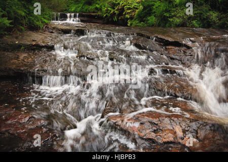 Water cascading over rocks in a mountain stream. - Stock Photo