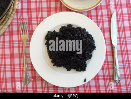 Arroz negro (Black rice). Traditional Valencian rice dish made with cephalopod ink, cuttlefish or squid served in - Stock Photo