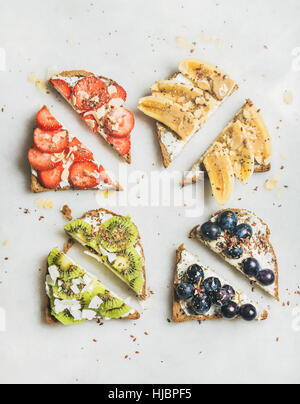 Healthy breakfast wholegrain toasts with cream-cheese, fruit, seeds, nuts - Stock Photo