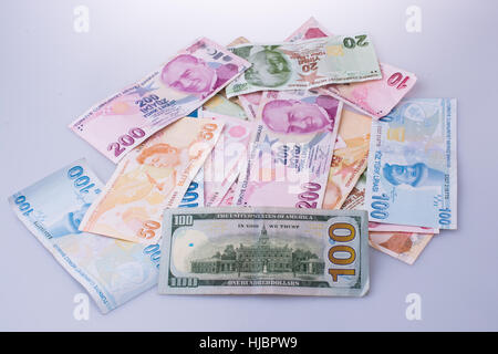 American dollar banknotes and Turksh Lira banknotes side by side on white background - Stock Photo