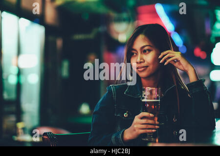Night life, adult girl waiting in the Bar drinking bear