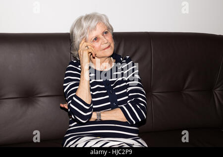 Portrait of the elderly woman sitting and thinking. - Stock Photo