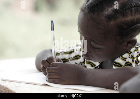 Cute African schoolgirl doing her homework at school: beautiful black girl writing and learning activity with a - Stock Photo