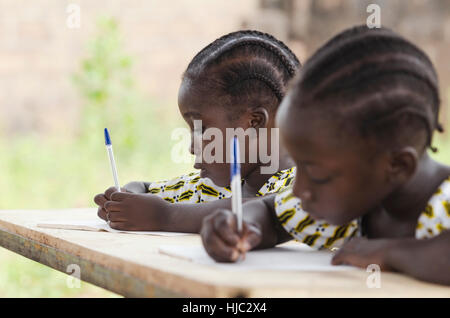 African Children at School Doing Homework. African ethnicity students writing their essay in an African school. - Stock Photo