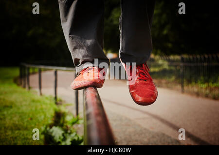 Man training in park, legs and red trainers balancing on fence - Stock Photo