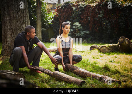 Woman with personal trainer crouching to lift tree trunk in park - Stock Photo