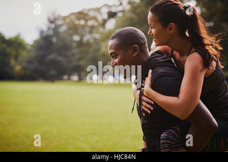 Man and woman having fun training in park, giving piggy back - Stock Photo