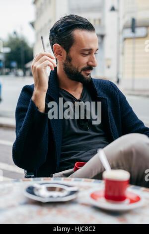Mid adult man smoking cigarette at sidewalk cafe - Stock Photo
