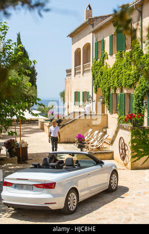 Porter welcoming couple driving convertible to boutique hotel, Majorca, Spain - Stock Photo