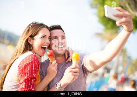 Couple taking selfie eating ice cream cones, Majorca, Spain - Stock Photo