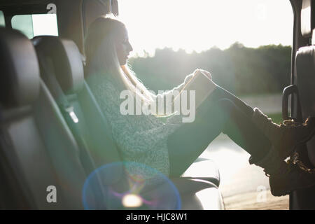 Sunlit portrait of young woman reading book at back seat of car - Stock Photo