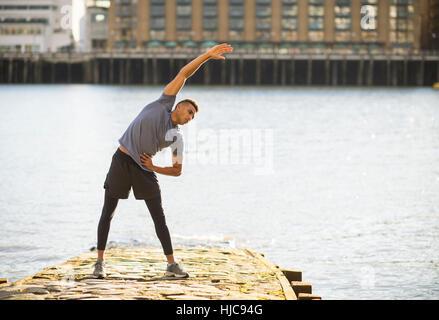 Man stretching on pier, Wapping, London, UK - Stock Photo